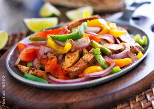 Poster mexican chicken fajitas in iron skillet with peppers