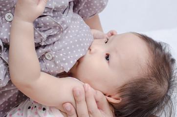 Asian mom breast feeding her baby girl