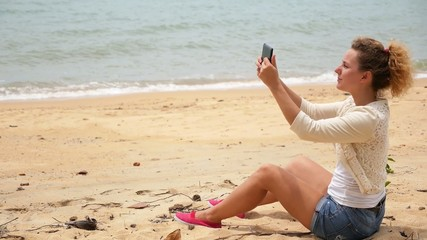 Female Taking Pictures with Tablet on Beach.