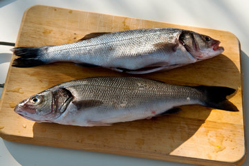 Two cleaned uncooked fresh bass