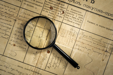 old deed property and magnifying glass, selective focus