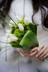Bride holding wedding bouquet from white tulipes and golden-dais