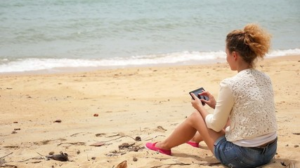 Woman Relaxing on Beach with Tablet Computer.
