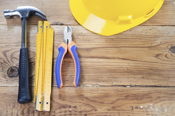hammer, folding ruler, nippers and yellow helmet