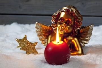 Goldene Putte mit roter Kerze und Christbaumkugeln