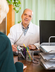 Friendly male doctor discussing with  female patient