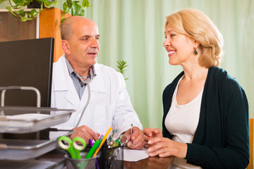 doctor talking with  mature female patient