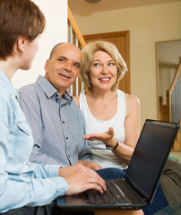 Happy aged couple talking with employee with laptop