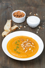 plate of carrot soup with almonds and watercress