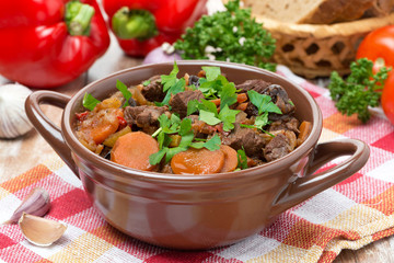 Stew with beef, vegetables and prunes in a saucepan