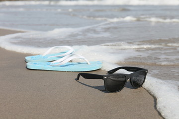 Sunglasses and flip flops on the sand