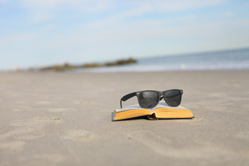 Sunglasses and book on the sand on a sunny beach
