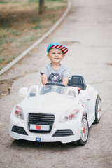 Fashion little boy driving toy car in a park