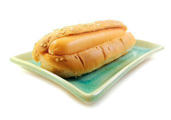 Bread with hot dog on plate on white background
