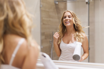 Blonde woman drying hair in front of mirror