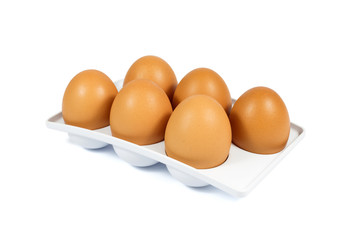 Six Brown Eggs in a White Plastic Package Isolated on White