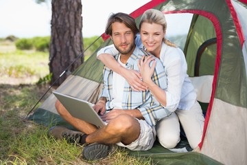 Attractive couple sitting by their tent