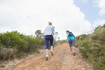Fit attractive couple jogging up mountain trail