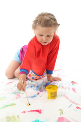 Little girl painting with paintbrush
