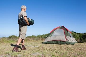 Happy camper walking towards his tent holding sleeping bag