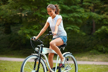 Happy Woman is Cycling in Summer Park