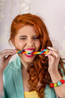 redhead girl biting a candy stick