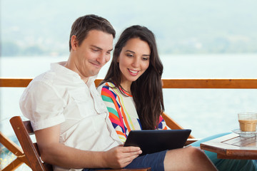 Couple are using tablet on vacation