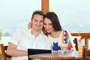 Young couple is using tablet on vacation in a cafee