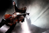 Concert photo of man playing cello with background lights