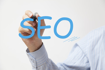 Hand writing SEO. Concept for technology