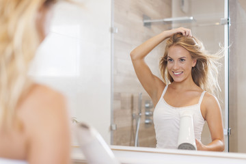 Natural woman in front of mirror drying hair