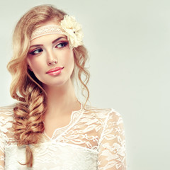 Beautiful model in lace dress with a pigtail and flower barrette