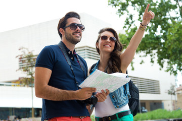 Young tourist couple use their map and pointing where they want