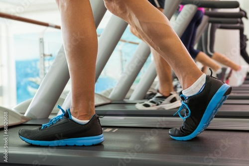canvas print picture Row of people working out on treadmills
