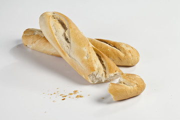 bruised baguette on a white background