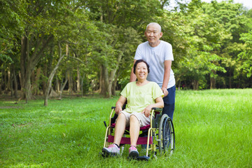 Asian senior woman sitting on a wheelchair with his husband