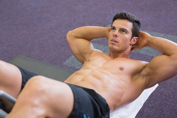 Muscular man doing abdominal crunches in gym