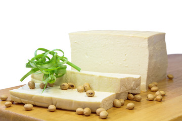 Soybeans , Tofu and green onion on a chopping block.