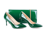 Beautiful green shoes with clutches on white isolated background