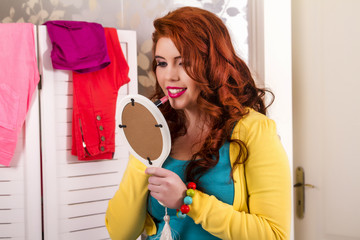 View of a beautiful redhead girl applying lipstick.