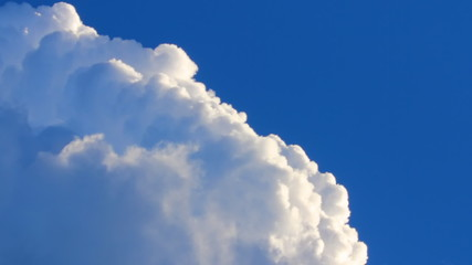 swirling white clouds on a background of deep blue sky