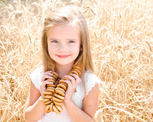 Smiling little girl on field of wheat with bagels