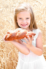 Smiling little girl on field of wheat with bread