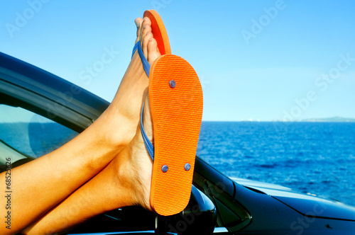 canvas print picture young man wearing flip-flops relaxing in a car near the ocean