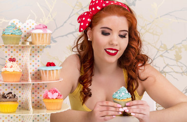 pinup redhead girl with colorful cupcakes.