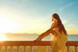 A woman on a balcony looking at the beautiful sunset