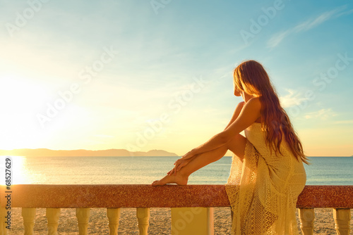 Plexiglas Ontspanning A woman on a balcony looking at the beautiful sunset