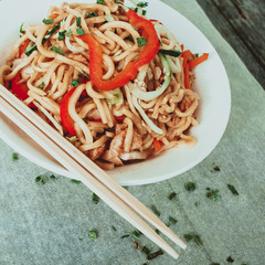 Bowl of chinese noodles with vegetables and shredded chicken