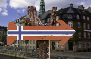 Norway wooden sign with a city on background