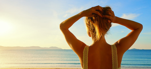 A back side view on a wonderful young woman watching to sea and
